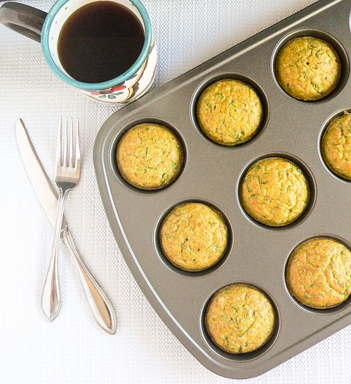 Top view of spinach almond amaranth breakfast muffins in the muffin tray along with a cup of coffee