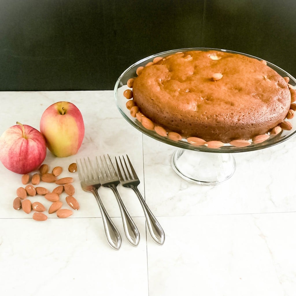A full view of Apple cake with apples and raw almonds as the props