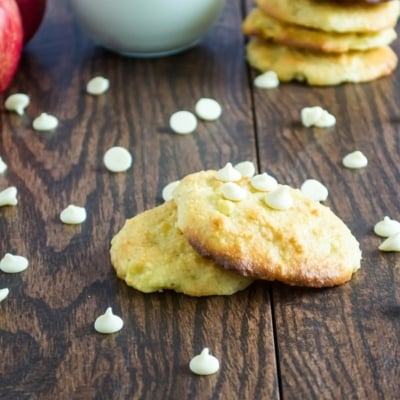 A front view of flourless apple macadamai cookies on each other with vegan white chocolate chips scattered on the table