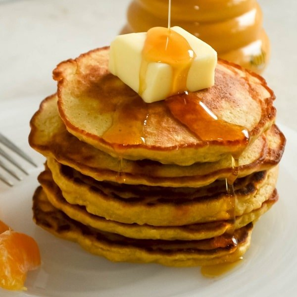 A stack of orange oatmeal pancakes with maple syrup drizzling over them