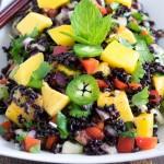 A 45 degree angle view of black rice mango salad