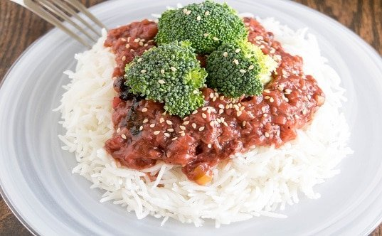 A 45 degree angle view of broccoli in strawberry sauce