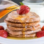 Maple syrup drizzling over a stack of caramelized strawberry sauce pancakes