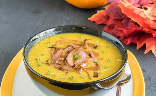 A front view of Apple Pumpkin Soup with fall colored leaves as the prop
