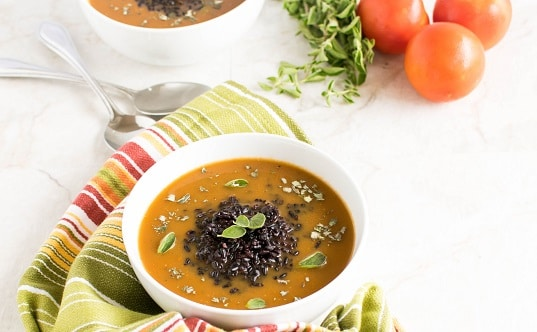 A front view of Herbed Black Rice Soup with the raw ingredients at the backdrop