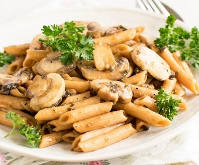 A front view of pasta mushroom stir fry in the serving dish