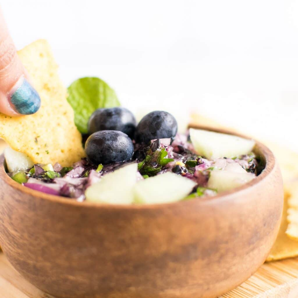 A hand in action of dipping into Honey Dew Blueberry Salsa