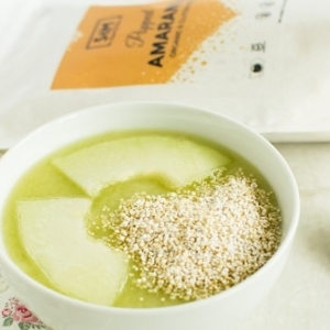 A close up view of popped amaranth honey dew cucumber smoothie bowl