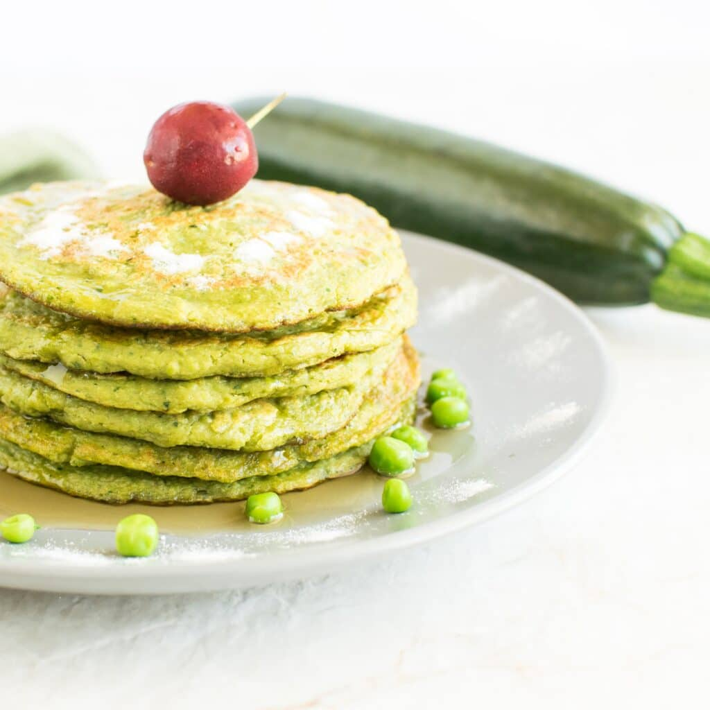 A stack of Green Peas Zucchini Sweet Pancakes with raw zucchini as the prop