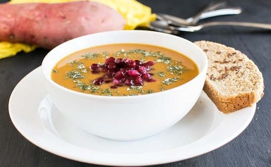 A front view of sweet potato pomegranate soup with a bread on the side