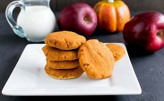 A stack of Apple Sauce Pumpkin Cookies with the ingredients as the props