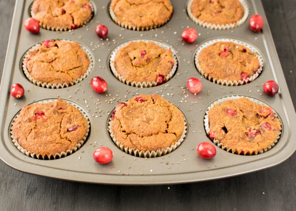 a muffin tray with baked cranberry muffins