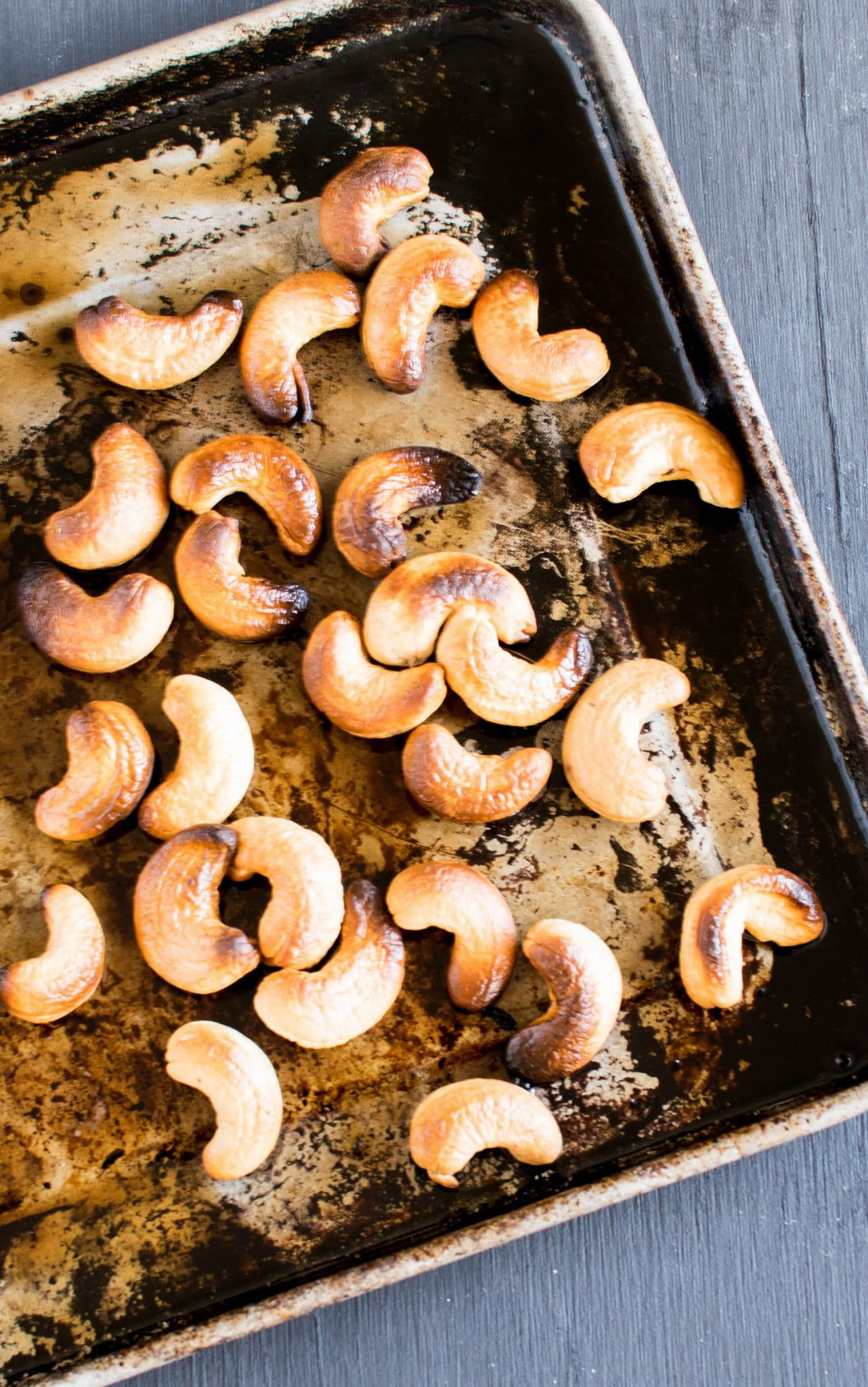 Roasted cashew nuts are shown on the baking tray