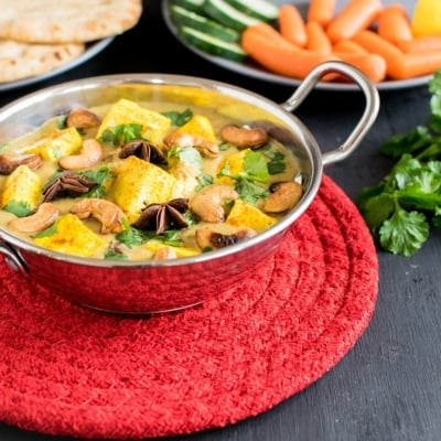 Turmeric Tofu Cashew Curry is presented in a steel kadai with salad and naan as the props.