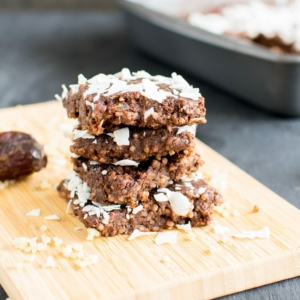 A front view of a stack of No Bake Chocolate Coconut Quinoa Brownies on a wooden board