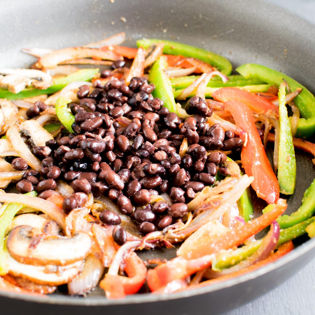 Black beans added to the sauteed veggies in the pan