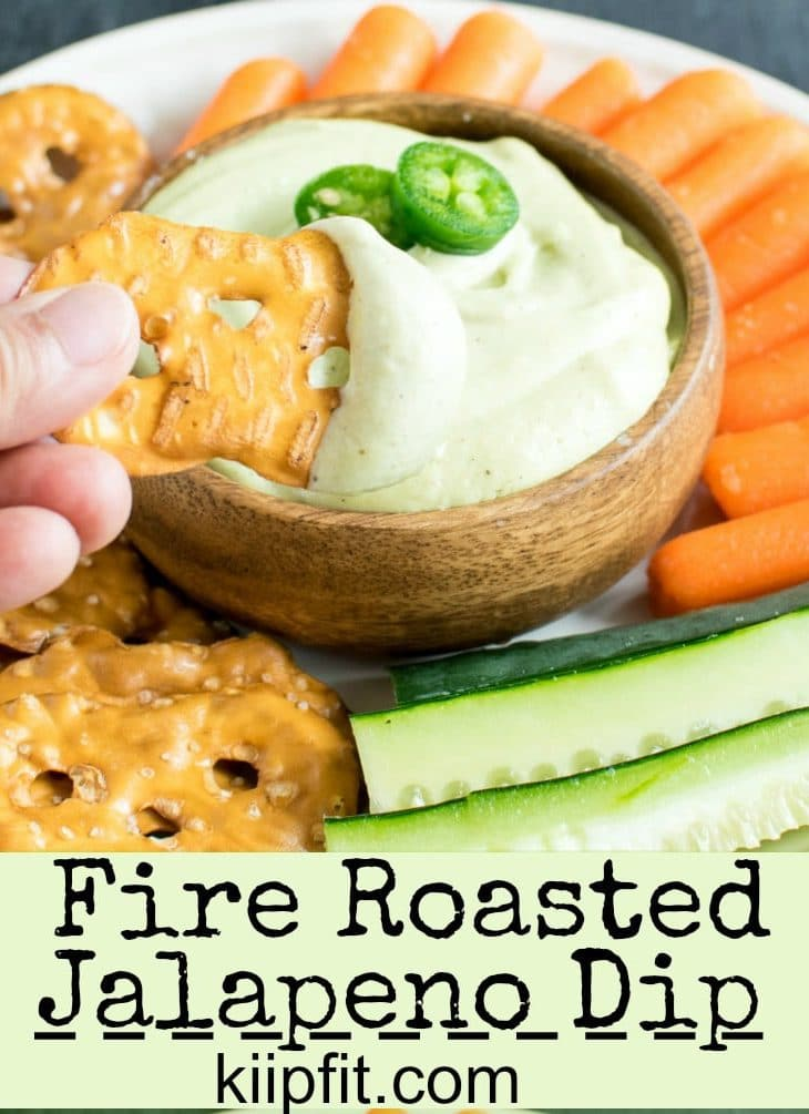 A pretzel dipping in fire roasted jalapeno dip