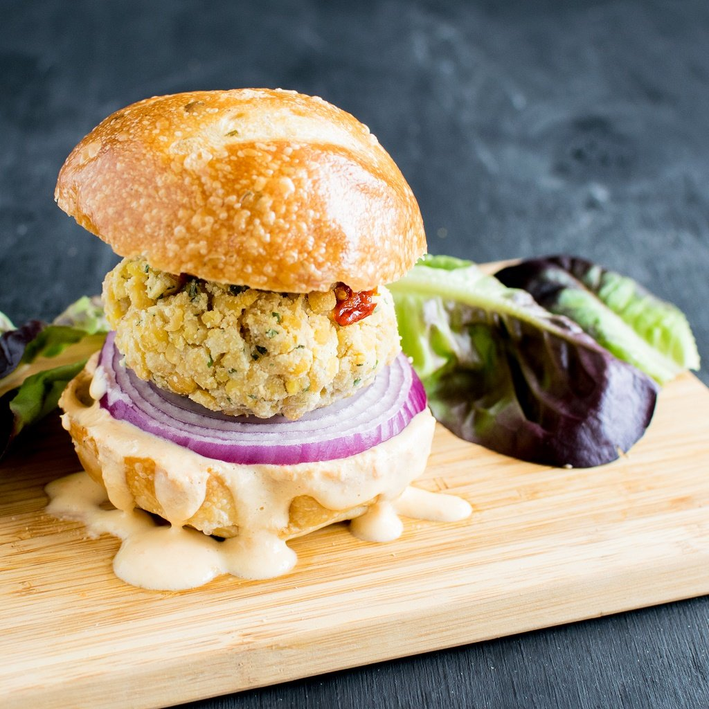 A 45 degree angle view of Tempeh Parmesan Burger with Habanero Dip