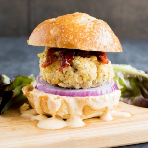 A front close up view of Tempeh Parmesan Burger with Habanero Dip