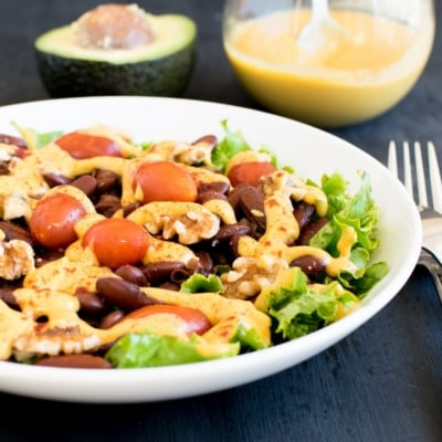 A 45 degree angle view of kidney beans salad wit cheesy avocado dressing