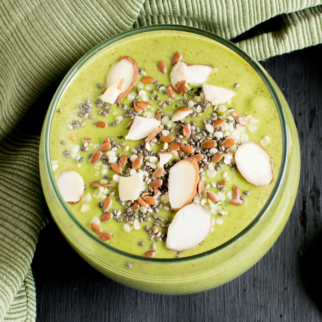 A closer top view of Superfood Green Smoothie garnished with chia, hemp, and almonds.
