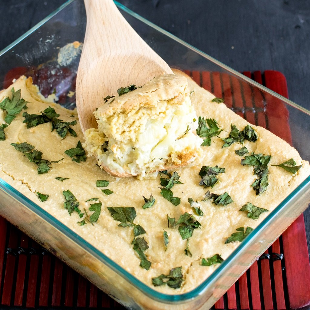 Top view of Vegan Cheese and Parsley Baked Cauliflower with a wooden spatula