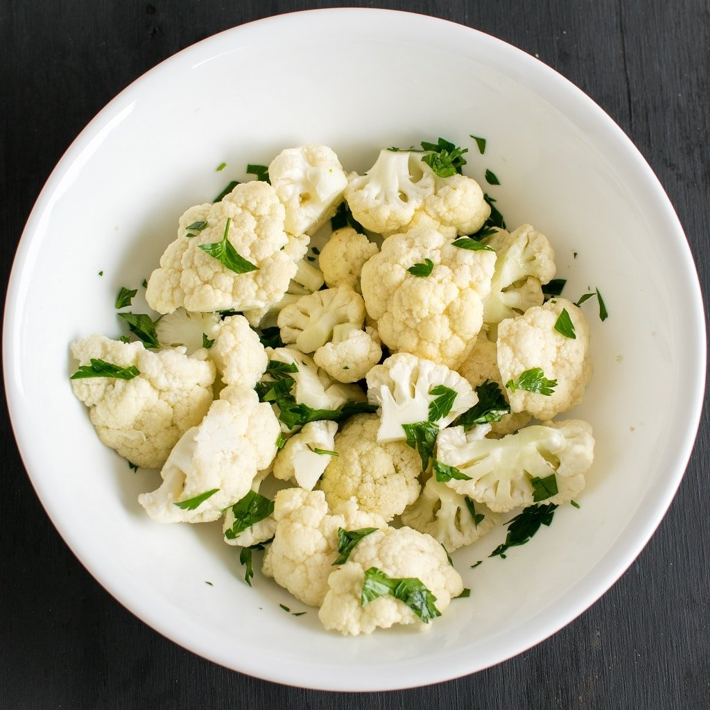 Cauliflower and Parsley mixed together in a white bowl