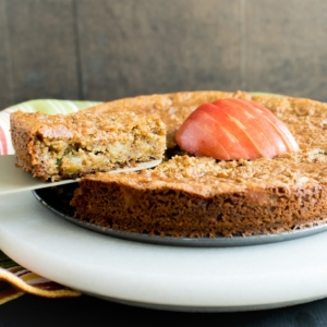 A slice of pan seared vegan apple almond cake being lifted with a cake spatula