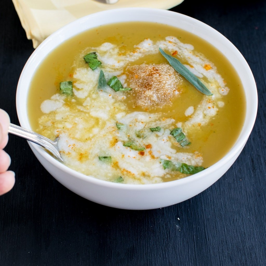 A spoon held in hand dipped in sriracha butternut squash soup