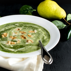 Fire Roasted Jalapeno Pear Spinach Soup is shown in a white bowl with the ingredients as the prop