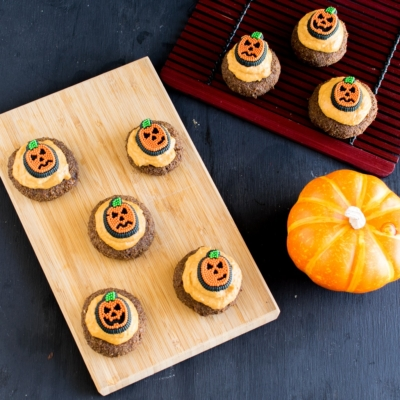 Top view of frosted Pumpkin Cheesecake Coffee Flax Cookies on a wooden board and a red mat on the side with a pumpkin as the prop