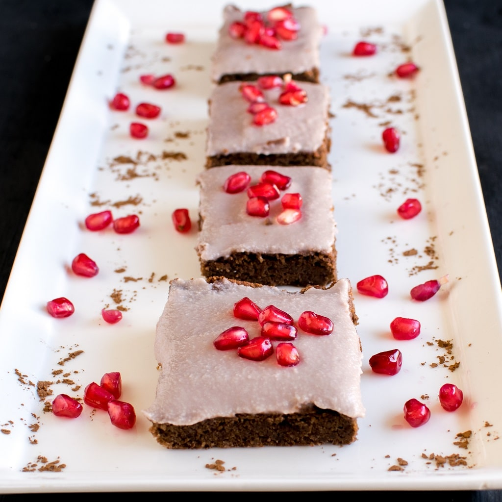 An array of Pomegranate Frosted Flourles Brownies is shown in a white rectangle plate