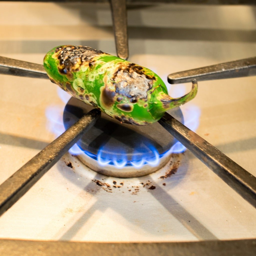 Whole jalapeno pepper places on a burner with a flame to fire roast it until the it has the burnt effect. Then chop the pepper and blend in Fire Roasted Jalapeno Pear Spinach Soup [ vegan + paleo ] kiipfit.com