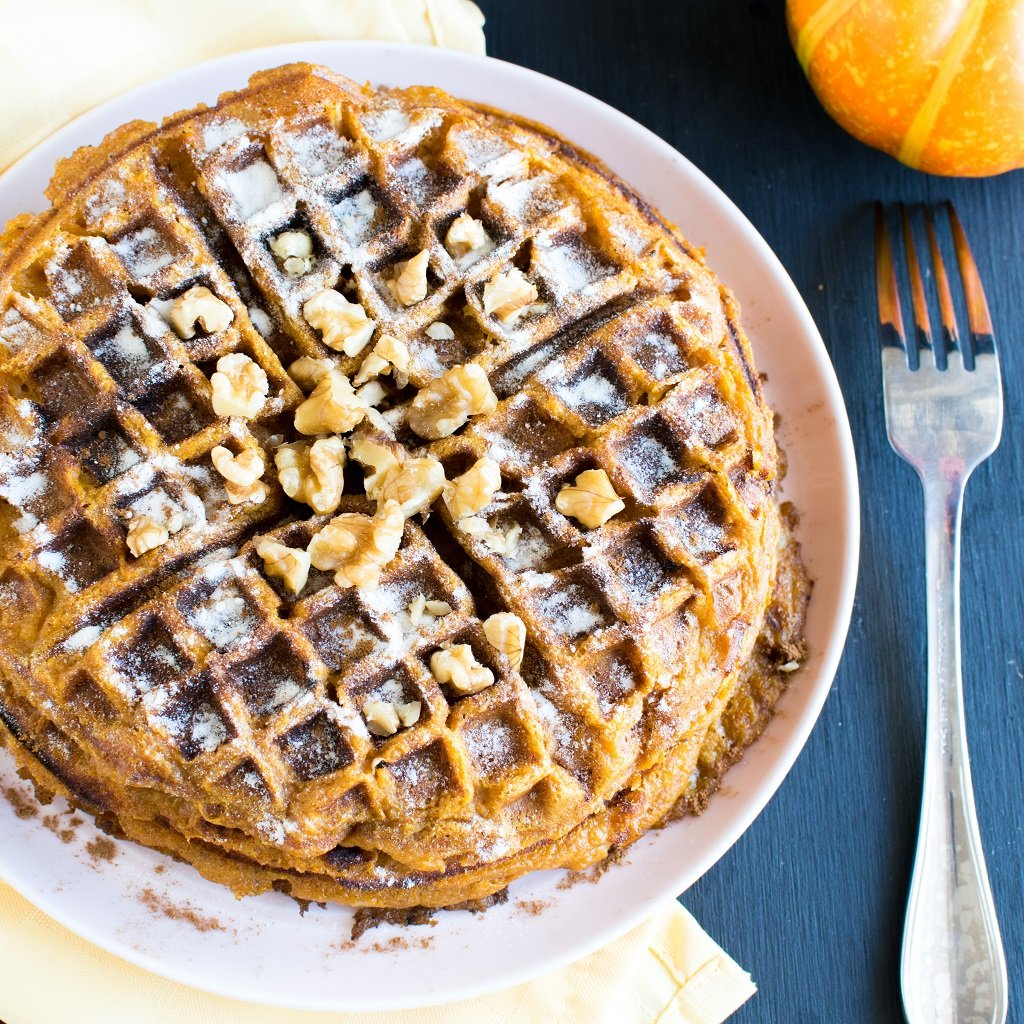 Pumpkin Pie Spice Spelt Waffles from top view with sprinkled sugar and raw walnuts