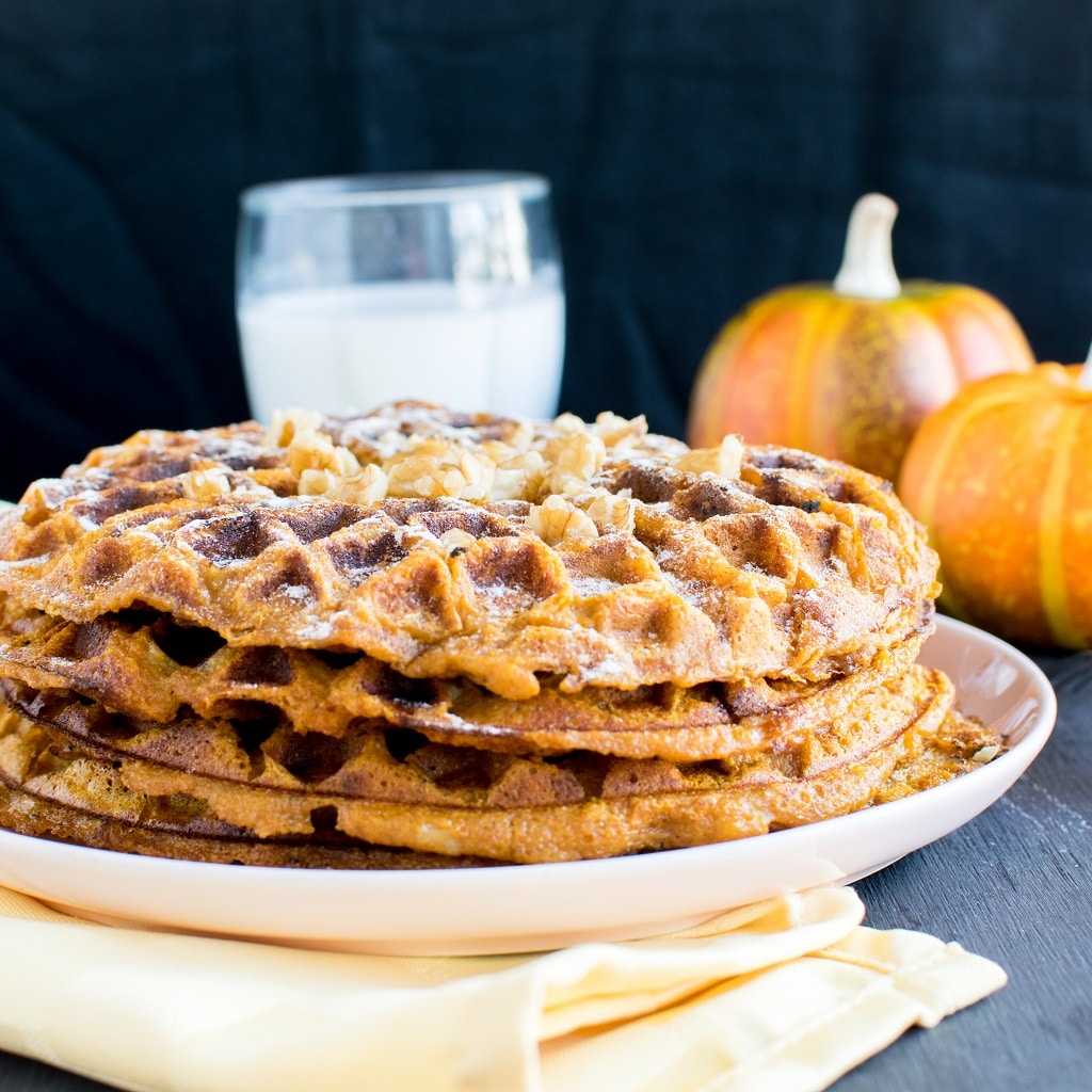 Pumpkin Waffles on a pink dessert plate. The image appears from the front angle showing the stack of waffles with a glass of milk and couple of pumpkins on the background