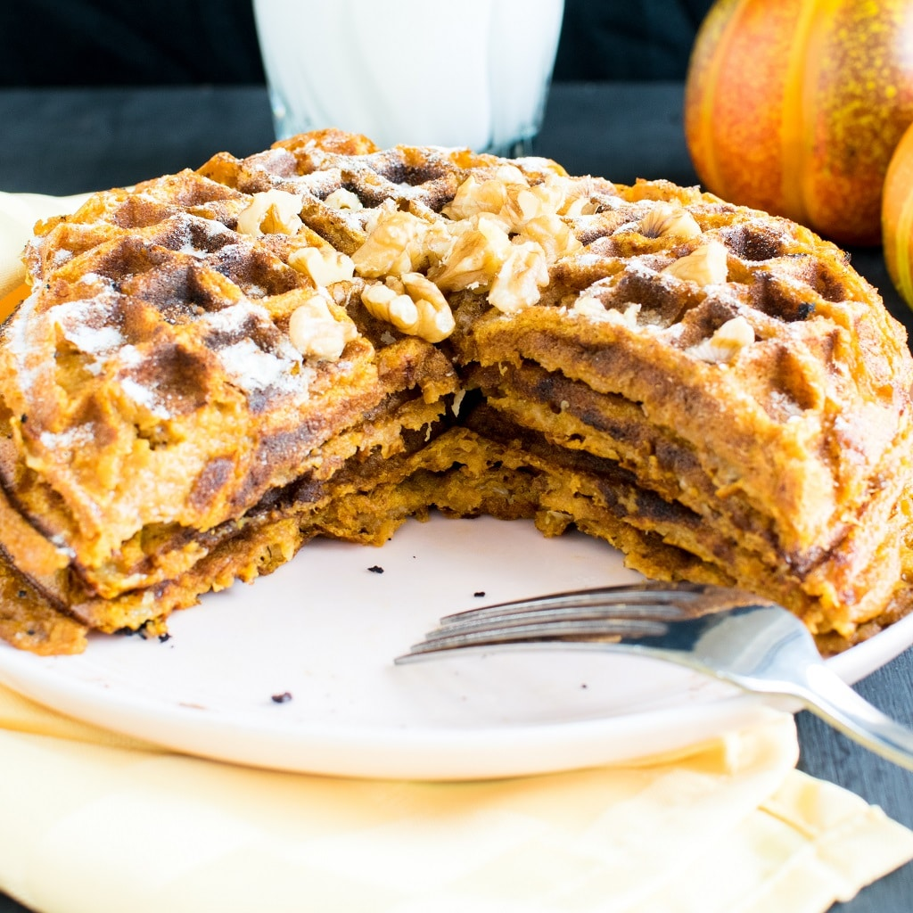 Pumpkin Waffles cut into a triangle slice on a pink dessert plate with a fork on the plate too. The waffles are covered with powdered sugar and topped with raw walnuts