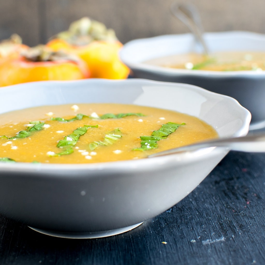 A front close up view of persimmon habanero soup with raw persimmons at the backdrop