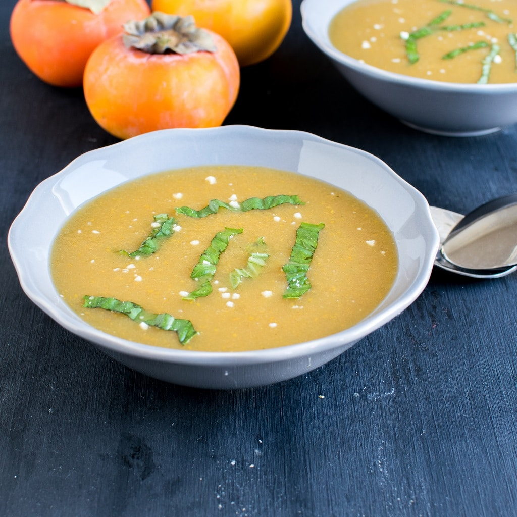 Persimmon Habanero Soup presented in two bowls as a mirror effect with fresh persimmons as prop at the background