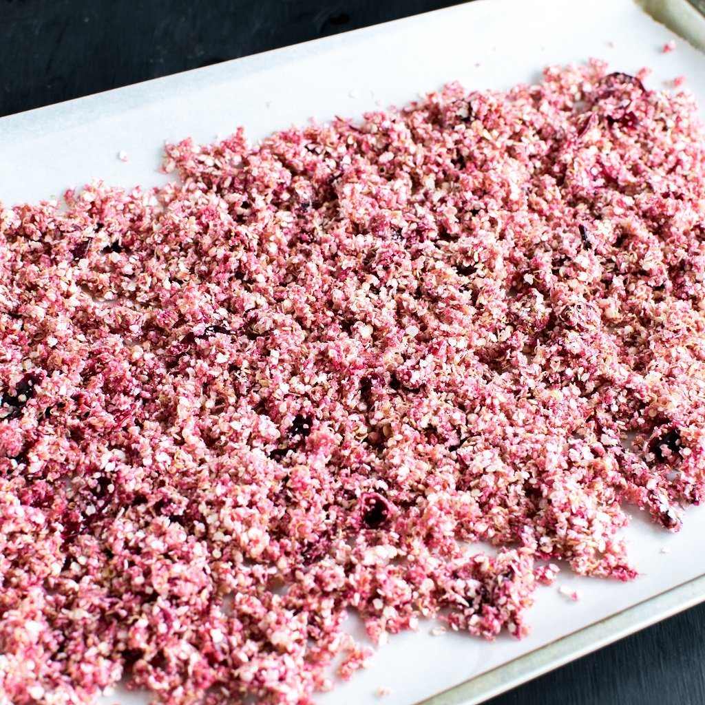 5 ingredient cranberry quinoa granola is shown on a cookie sheet before placing it in the oven.