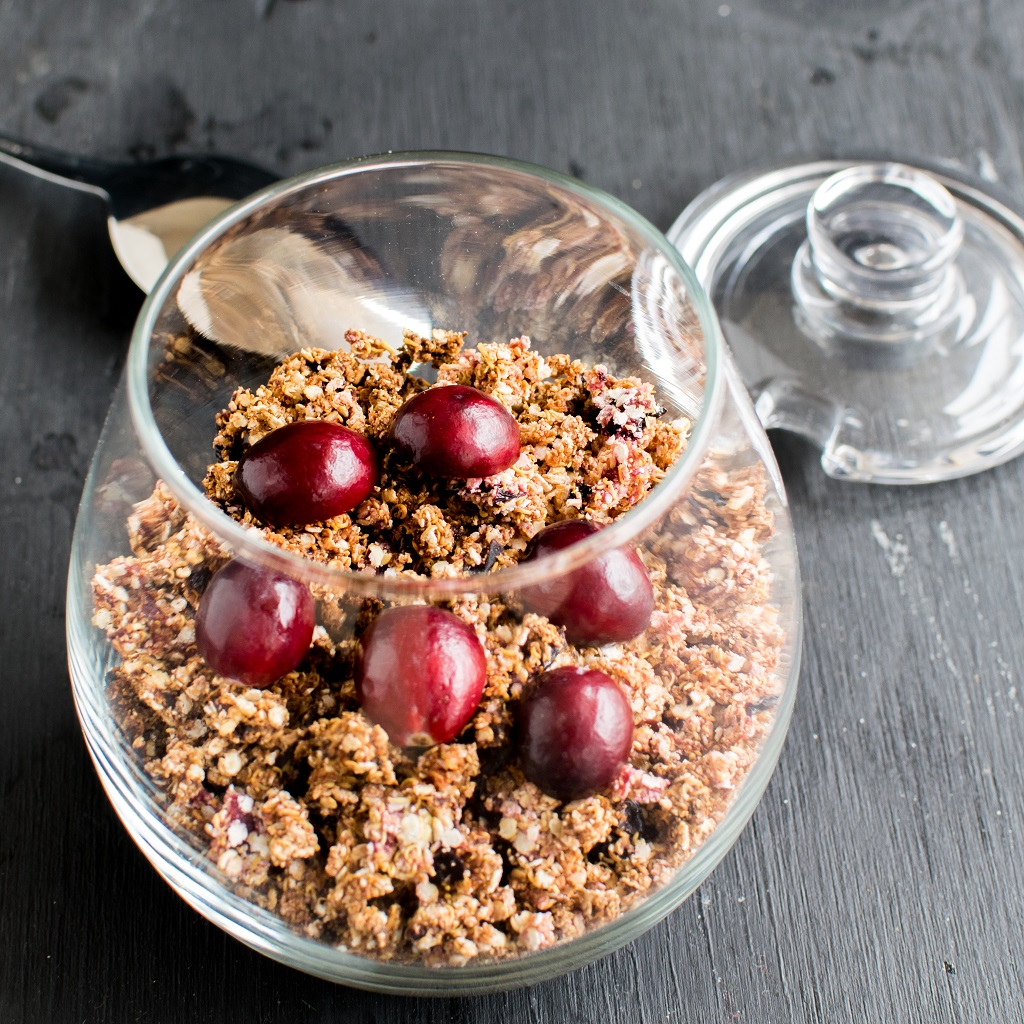 Once baked and cooled 5 ingredient cranberry quinoa granola is shown in a glass jar ready too be stored.
