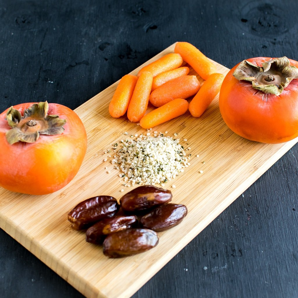 The raw ingredients of persimmon carrot hemp smoothie is displayed on a wooden cutting board | kiipfit.com
