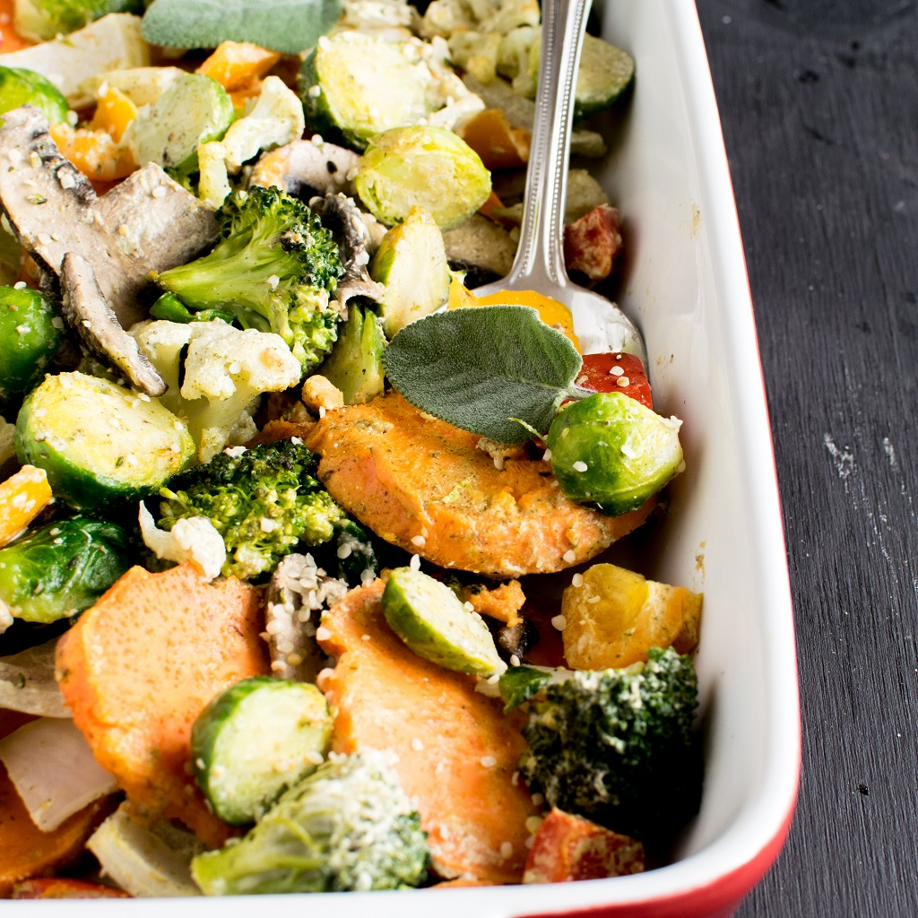 A close up of Vegan Herb Hemp Roasted vegetables is shown in a baking casserole pan along with a serving spoon