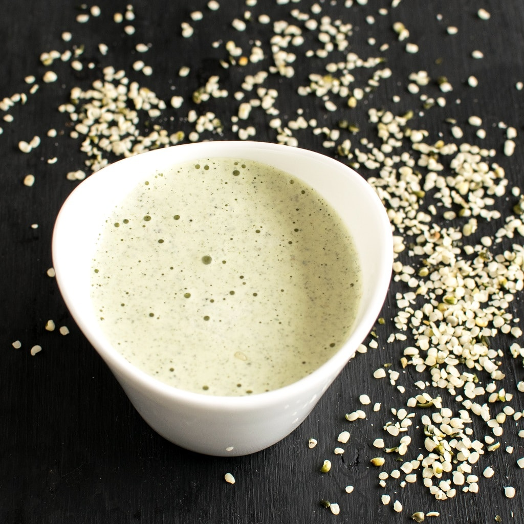 Herb Hemp Seed Dressing used in this recipe is shown in a white dip container with lots of hemp seeds spread as a prop