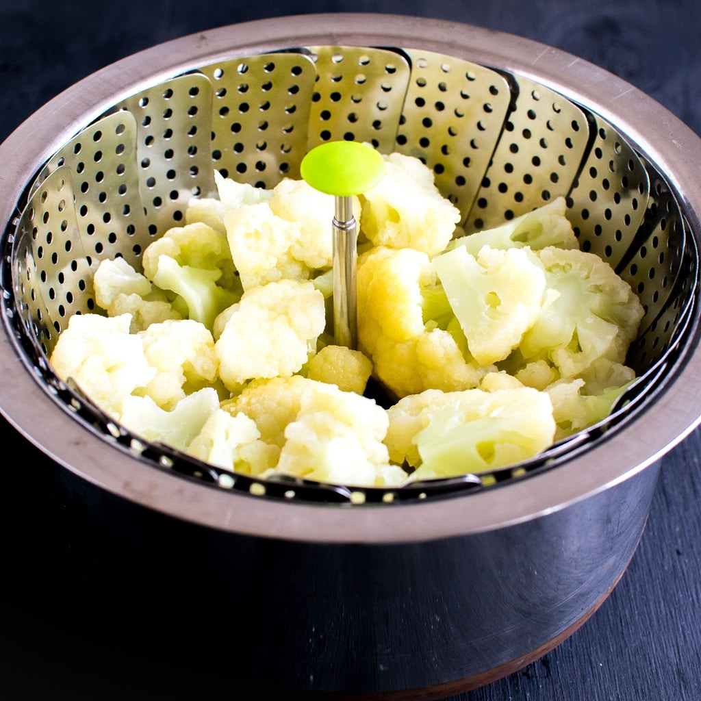 Steamed cauliflower florets are shown in a steamer basket placed inside a saucepan