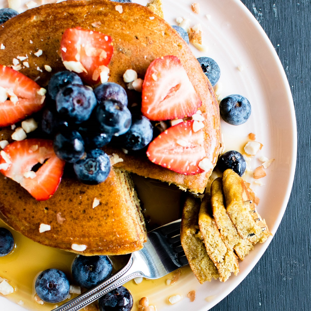 The top view of chickpea flour peanut butter protein pancakes with a fork full of a triangle stacked pieces of pancakes is shown in this image