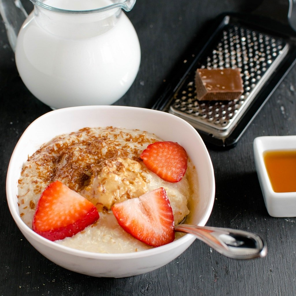 Peanut Butter Quinoa Flake Porridge is shown in a breakfast bowl with shaved chocolate, peanut buttrea nd starwberries as the toppings. The raw ingredients are placed as props in this image | kiipfit.com