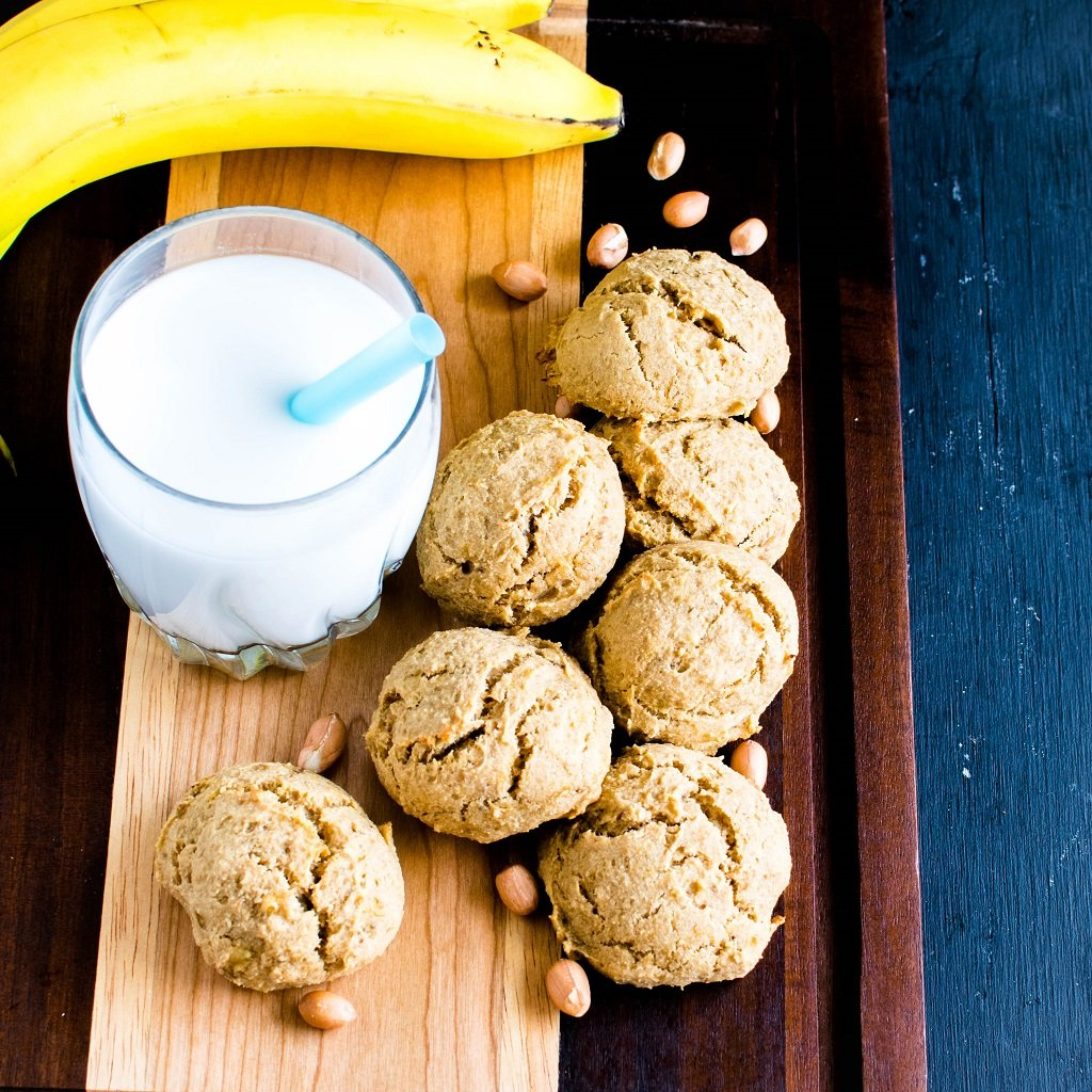 A wooden board stacked with Peanut Butter Banana Amarnth Cokies along with a glass of milk is shown in this image | kiipfit.com