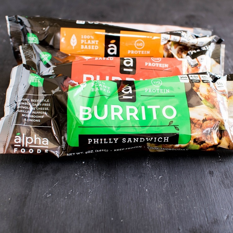 A stack of packed Alpha Burritos are shown in this image