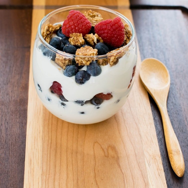 Healthy Breakfast Vegan Yogurt Parfait is displayed in a serving glass with a wooden spoon.