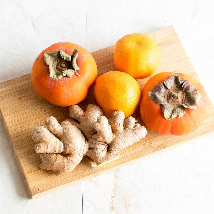 All the ingredients of Immune Boosting Persimmon Ginger Smoothie are shown on a wooden board